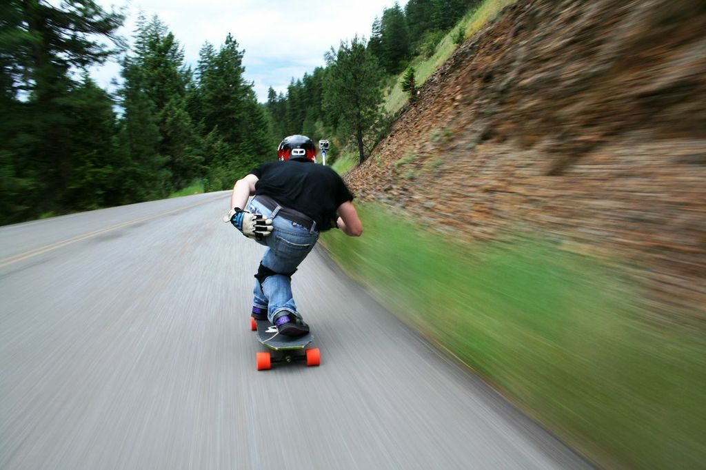 Man riding a longboard on a paved road.