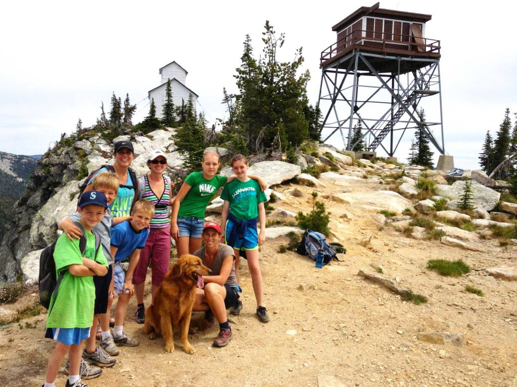 Family posing for camera at the summit of Lookout Mountain Tower, with old firelookout in the background.