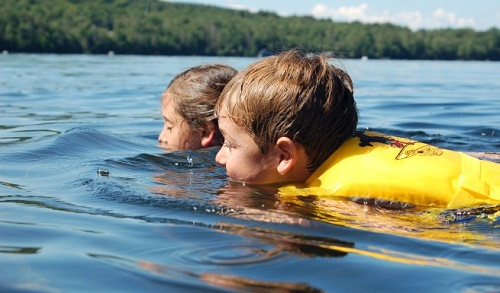Two children swimming on their bellies in a lake, with chins in the water, while wearing life jackets.