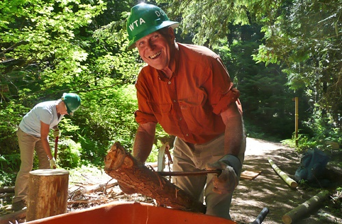 Male volunteer wearing a green hard hat smiles as he works on scraping bark from a tree, as part of the trail work duties with Washington Trails Association.