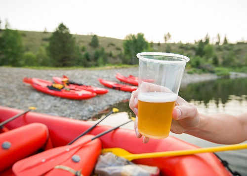 Hand holding a plastic cup of beer at the beech with inflatable rafts and kayaks on the rocky beach in the background.