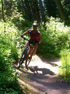 Woman mountain biking on a dirt trail.