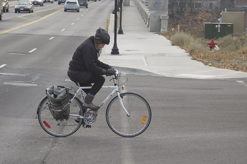 Cyclist crossing Monroe towards Kendall Yards.