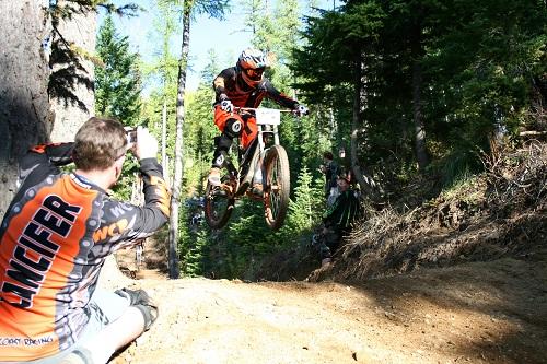 Mountain biker getting air on a jump on a dirt trail at Silver Mountain Bike Park in Kellogg, Idaho.