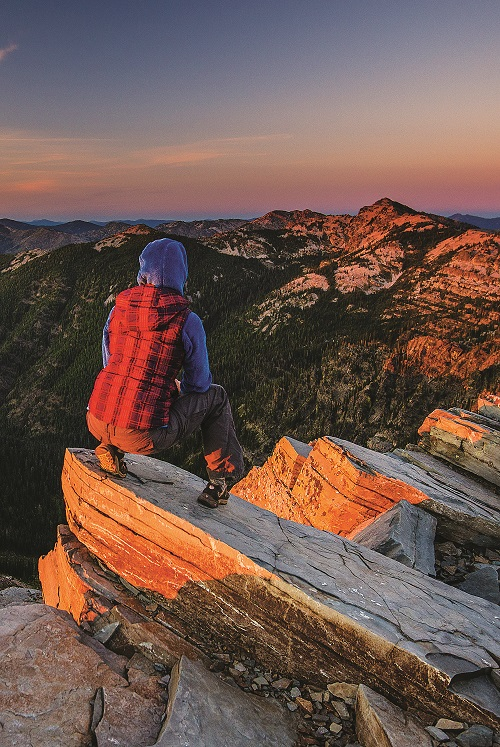 Hiker with a backpack looking at the sunset view atop rocks at Scotchman Peaks wilderness.