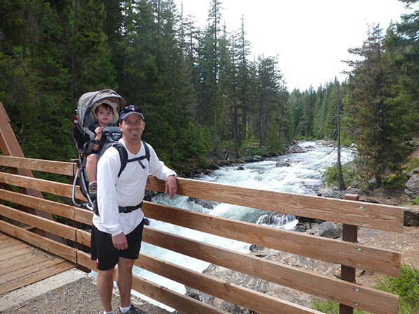 Dad with his toddler son in a backpack carrier -- standing on a bridge over the whitewater of Icicle Creek in the national forest near Leavenworth, Washington.