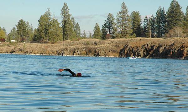 Woman open water swimming in a lake.