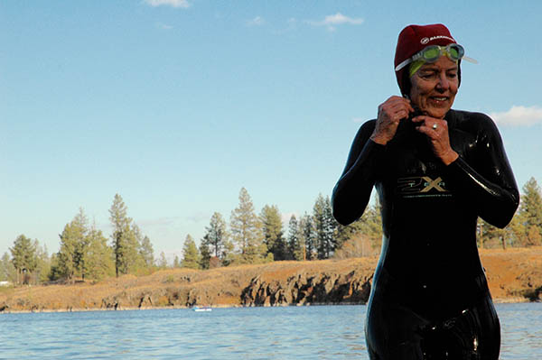 Woman in a wetsuit adjusting her swim cap, preparing for an open water swim.