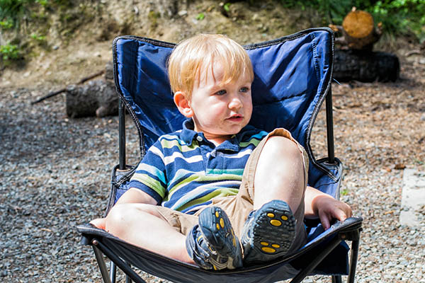 Child sitting in a camp chair at a campsite, with trees in the background.