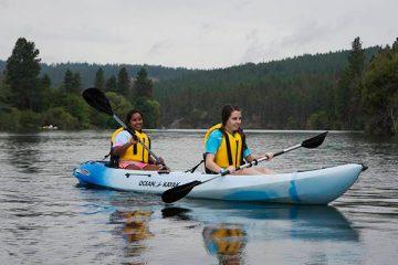 Photo of two girls kayaking on the Spokane River.