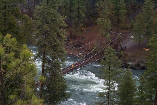Swinging bridge over the Spokane River and its raging whitewater rapids at the Bowl and Pitcher area of Riverside State Park.