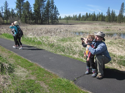 Parent and child on a trail at Turnbull National Wildlife Refuge -- looking through binoculars for birdwatching.