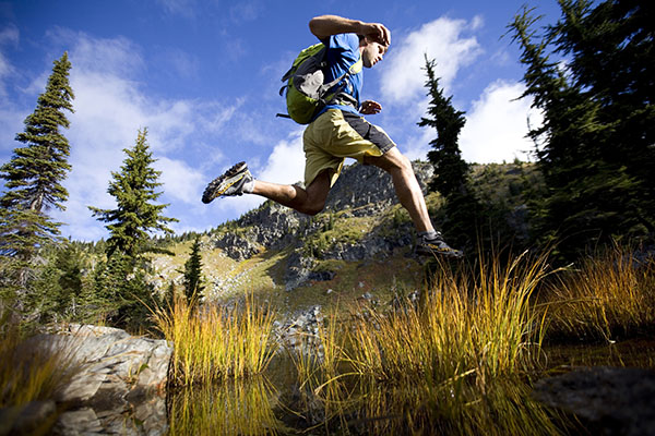 Runner jumping over a over while running in the Cabinet Mountain wilderness.