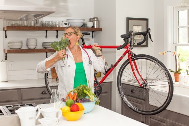 Ammi Midstokke wearing a lab coat, standing in a kitchen, and holding a red mountain bike with her left hand and a head of broccoli in her left hand as she takes an exaggerated bite.