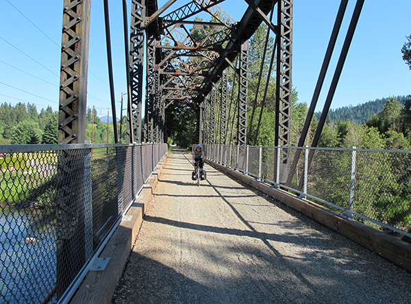 Biker crossing a bridge along the Palouse to Cascades Trail, formerly called the John Wayne Pioneer Trail. Photo by Marilyn Hedges.