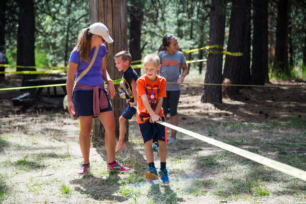 Photo of kids playing on slackline with parent watching.