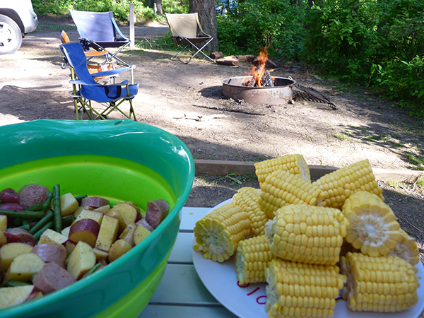 Bowl of cut vegetables and raw shrimp, and plate of corn cobs on a picnic table at a campsite.