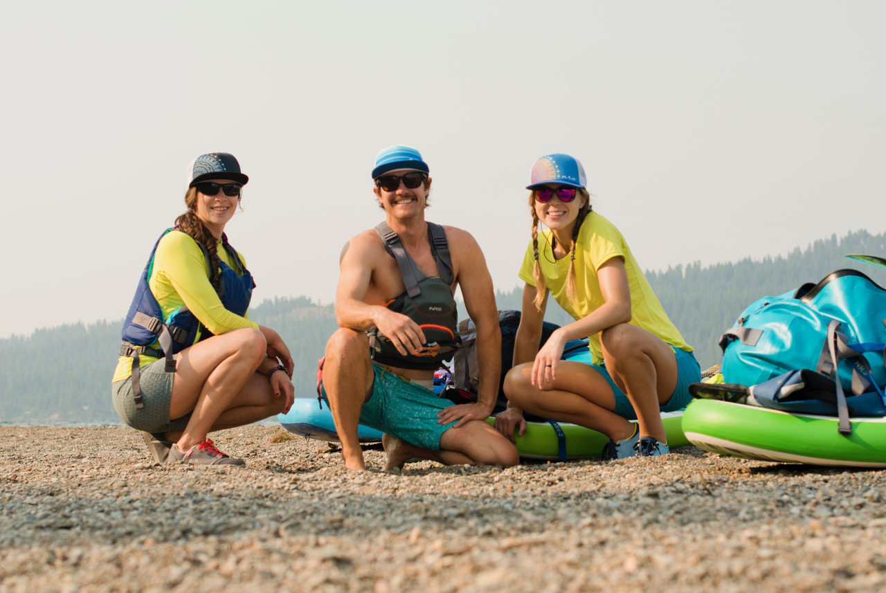 Grace, Jed, and Allie crouch near their paddle boards on land (Photo: Jed Conklin Photography)