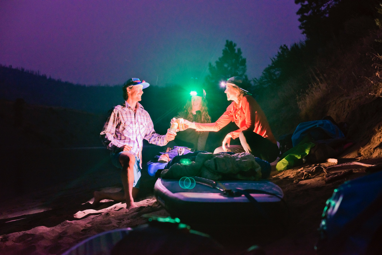 "Paddle boarders ""cheers"" beers with head lamps and paddle boards on shore (Photo: Jed Conklin Photography)"