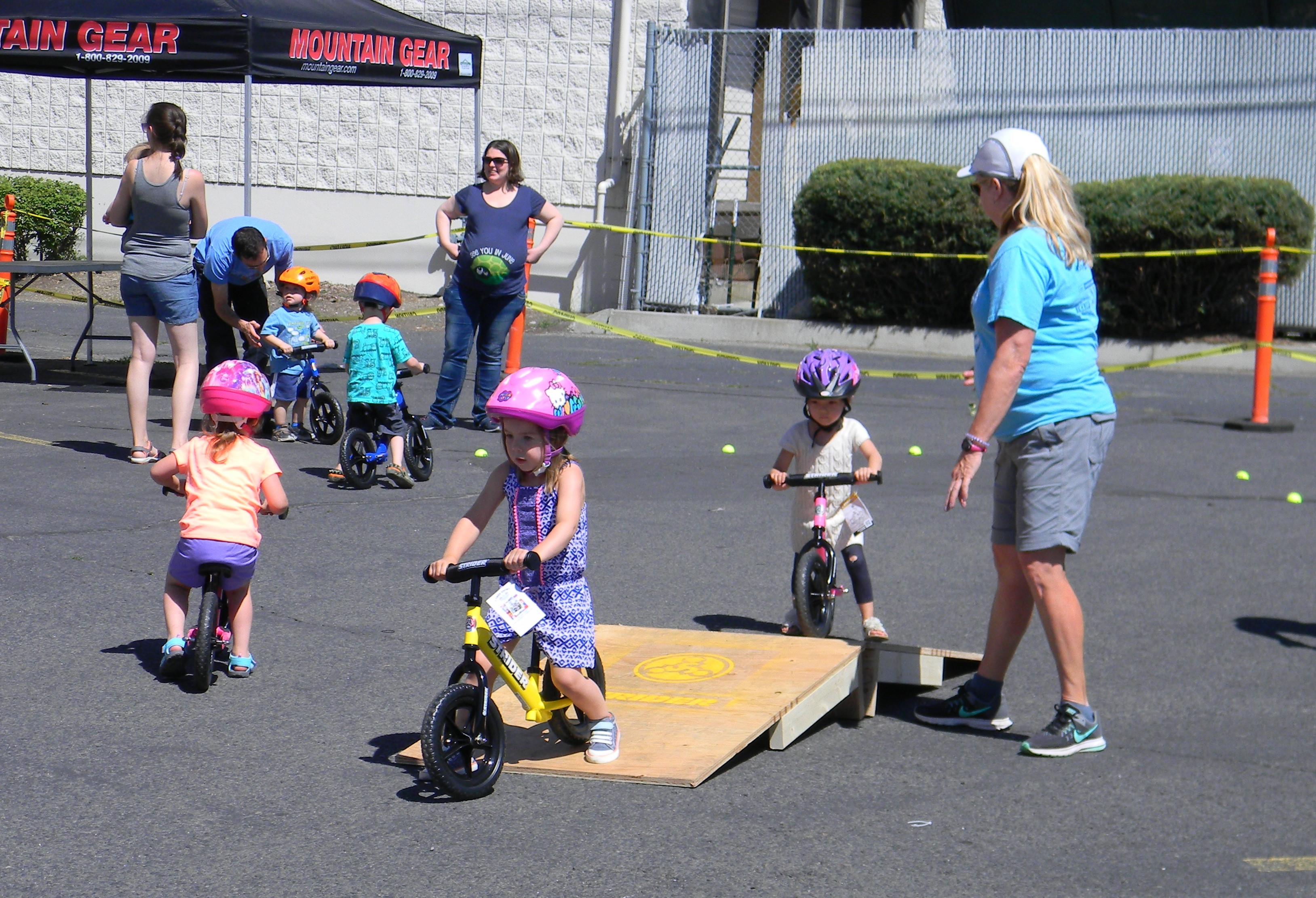 Kids ride strider bikes over a small ramp to hone their balance skills.