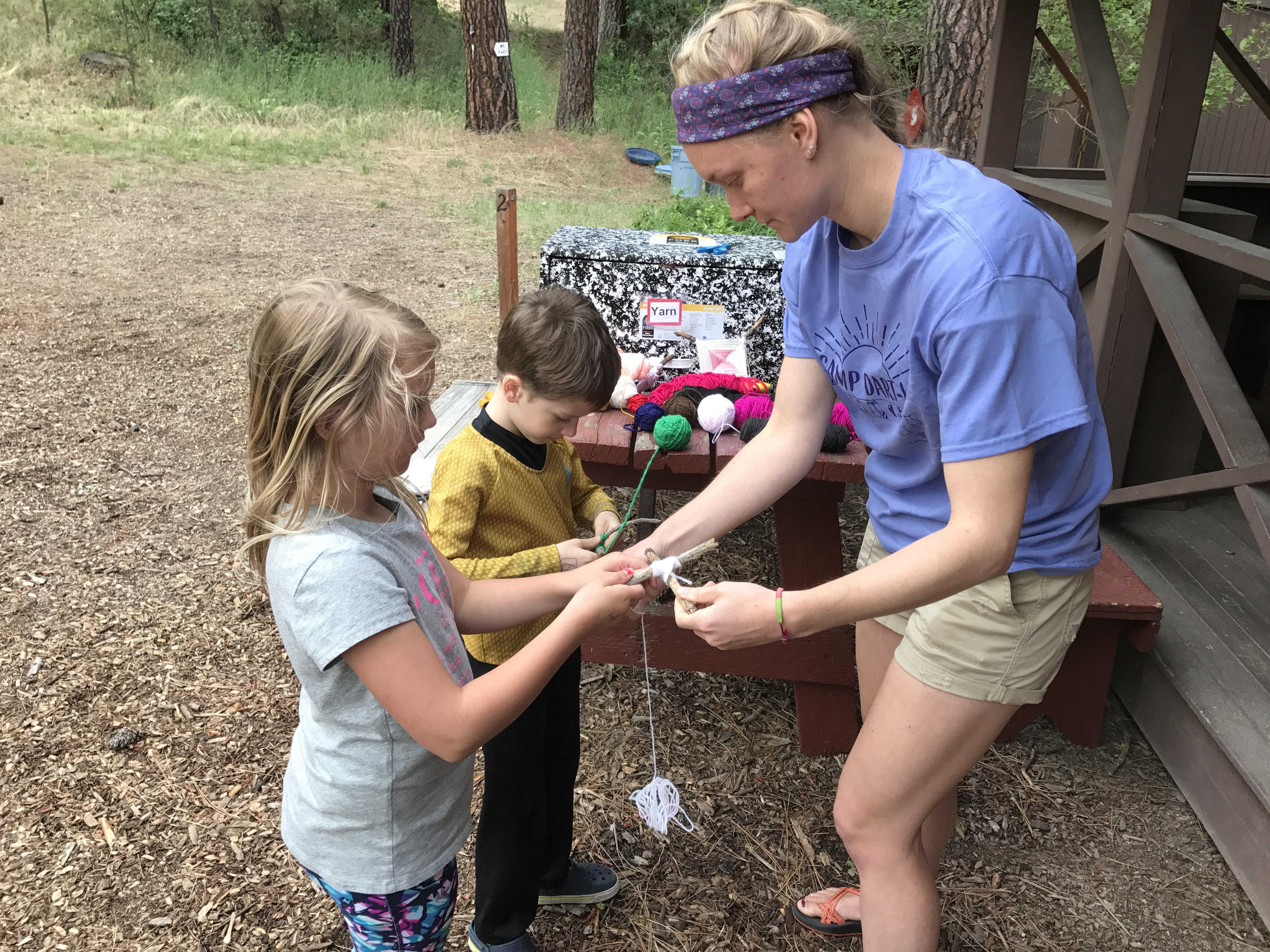 A camp leader helps a camper make a traditional God's Eye craft (Photo: Camp Fire Inland Northwest)