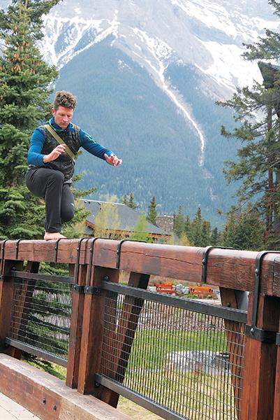 Photo of a guy balancing on a bridge rail by Katie Botkin.