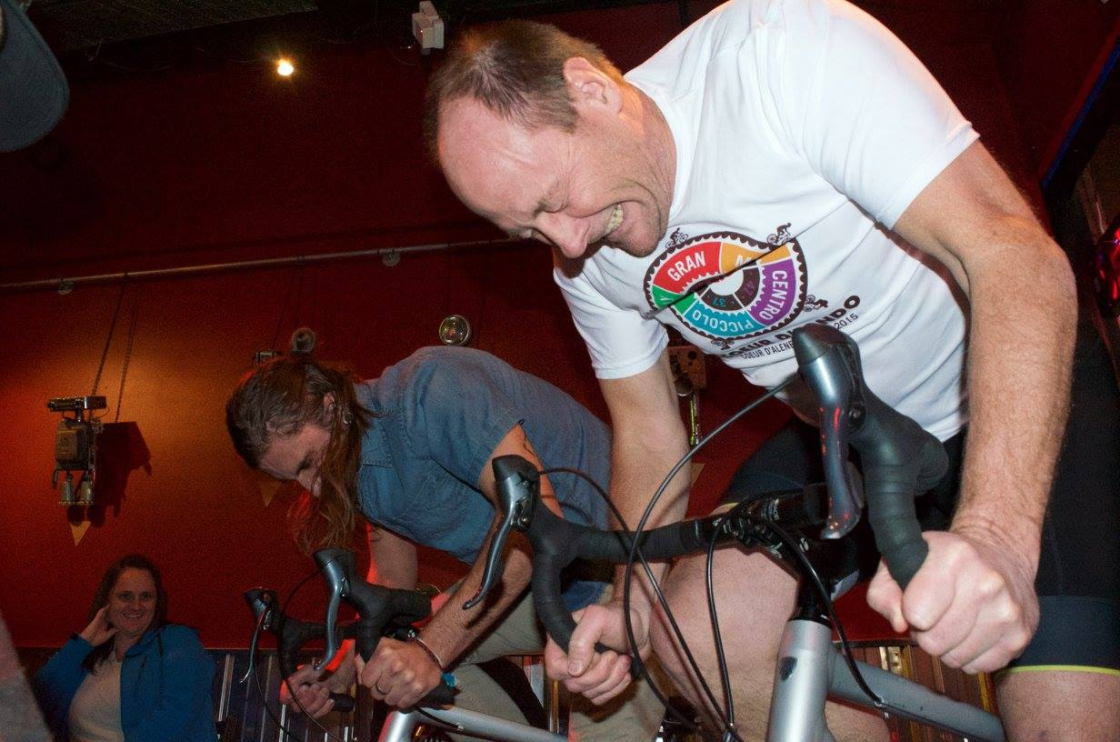 Two men pedal on stationary bikes in a race off.