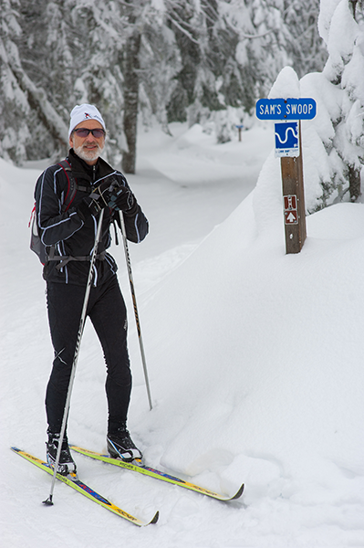 Photo of Sam Schlieder in front of trail sign for Sams Swoop.