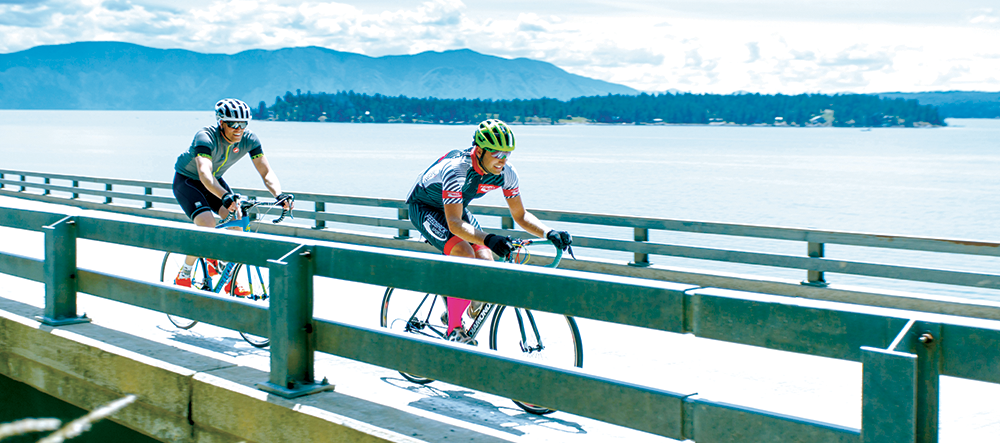Two male racers cycling on Long Bridge across Lake Pend Oreille, with mountains in the distance, during the Chafe 150 event in Sandpoint, Idaho.
