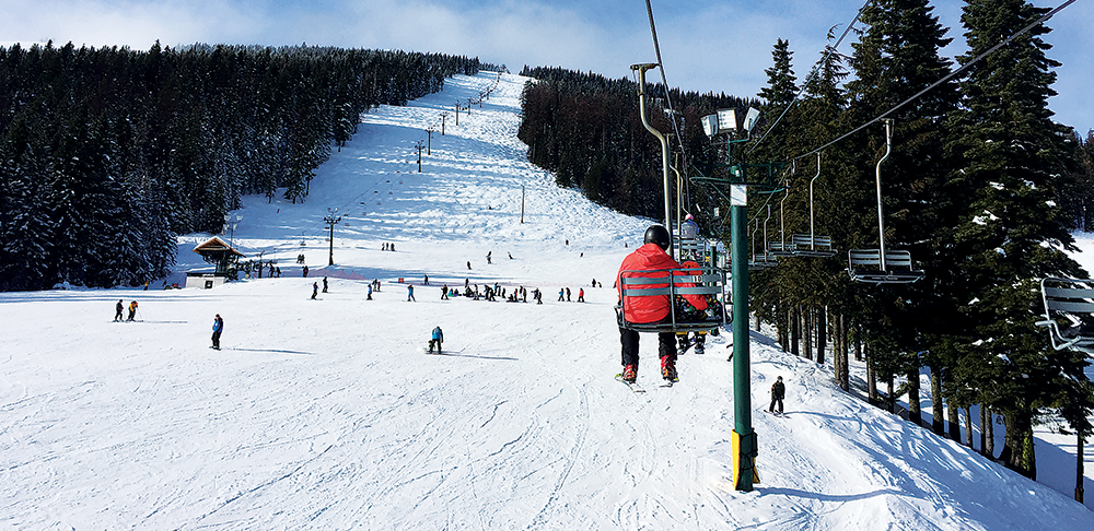 Photo of dad and son riding the chairlift together.
