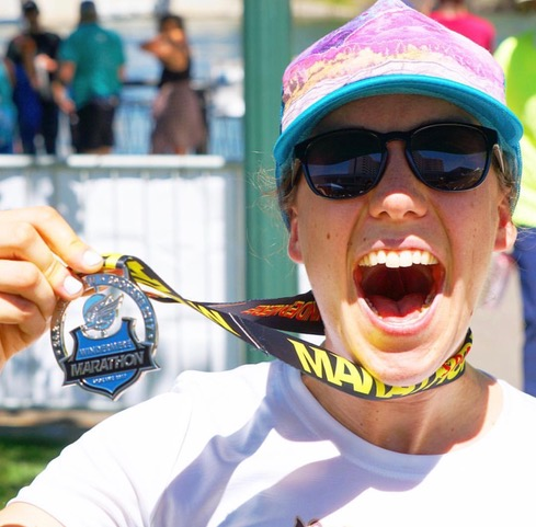 A woman holds a windermere marathon medal around her neck.