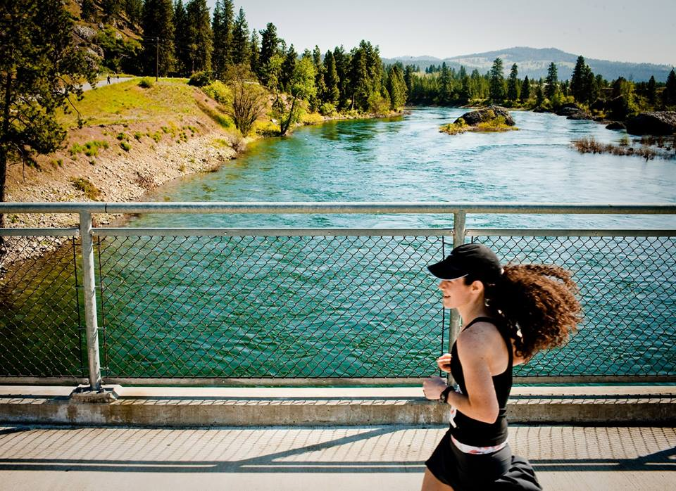 Woman running across a bridge over the Spokane River along the Windermere Marathon Centennial Trail route.