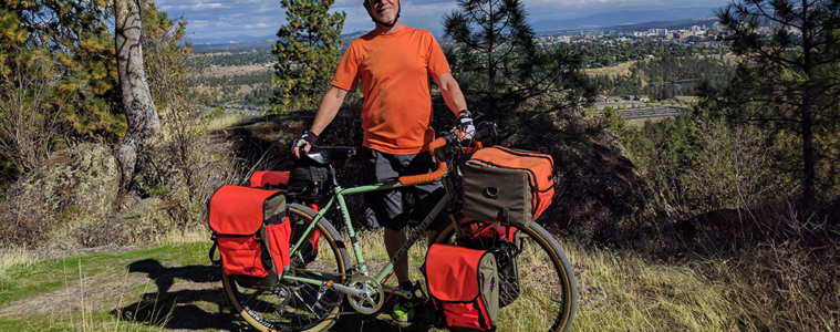 Hank Greer with bike wearing a neon orange shirt with neon orange travel packs attached to his bike.