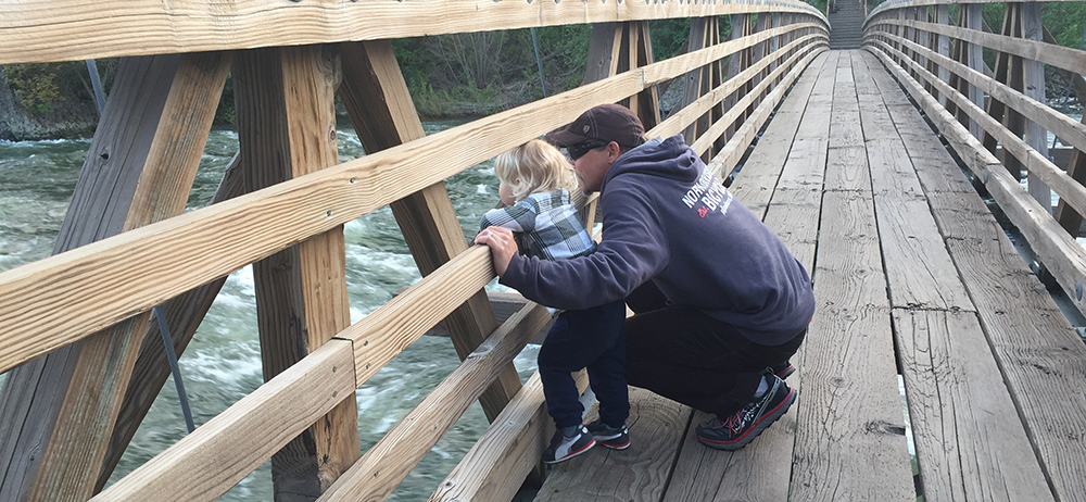 Photo of father and son on wooden bridge over the Spokane River.
