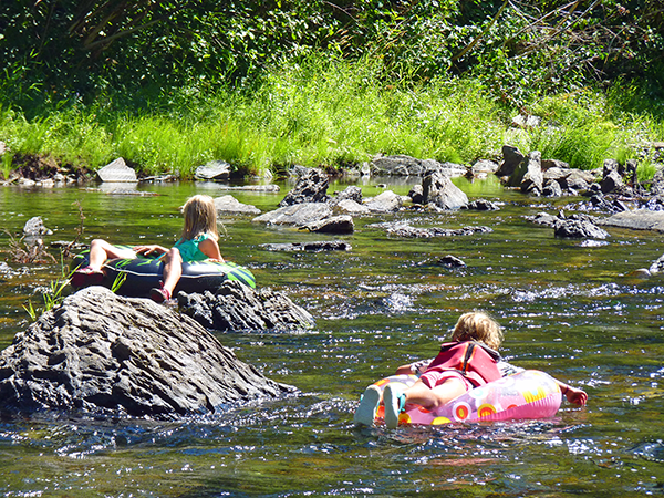 Photo of kids floating on tubes in a shallow part of the river.