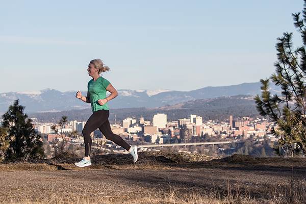 Photo of Kate Hellenthal running with Spokane skyline in the background.