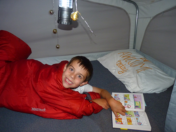 Photo of kid in sleeping bag in popup camper with a picture book.