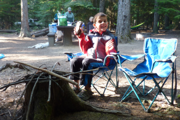 Photo of kid in front of make believe fire made from twigs and a tree stump.