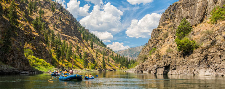 Photo of two rafts with mountains in the background.