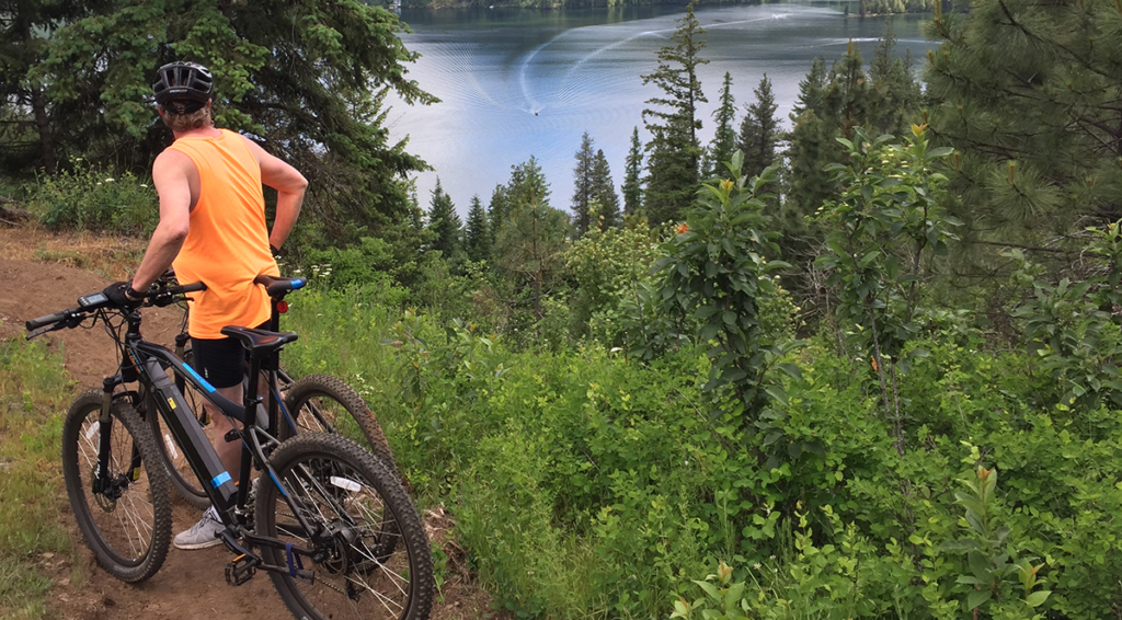 Photo of e-bike rider on side of trail admiring the view.