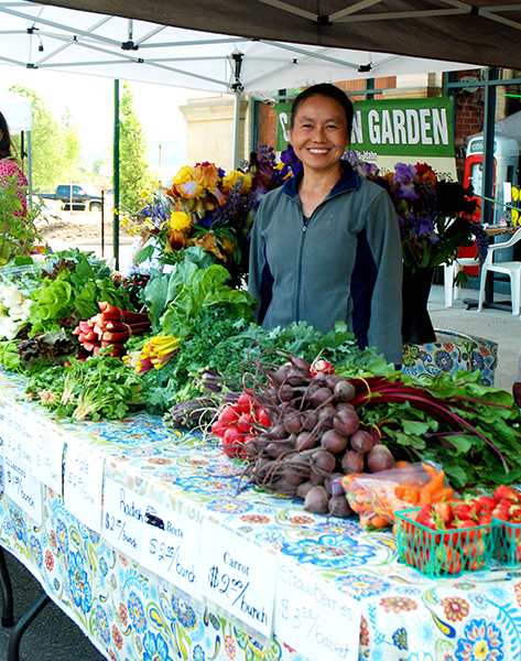 Photo of vendor with fruit and vegetables for offer.