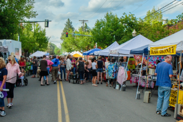 Photo of farmers market with people shopping at various stalls.