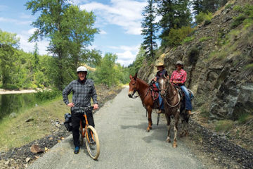 Photo of biker and two horses with riders stopped on the trail.