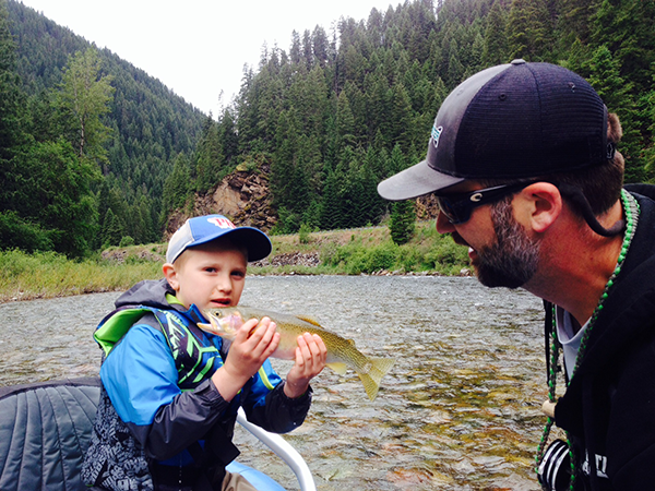Son holding up fish with dad looking on.