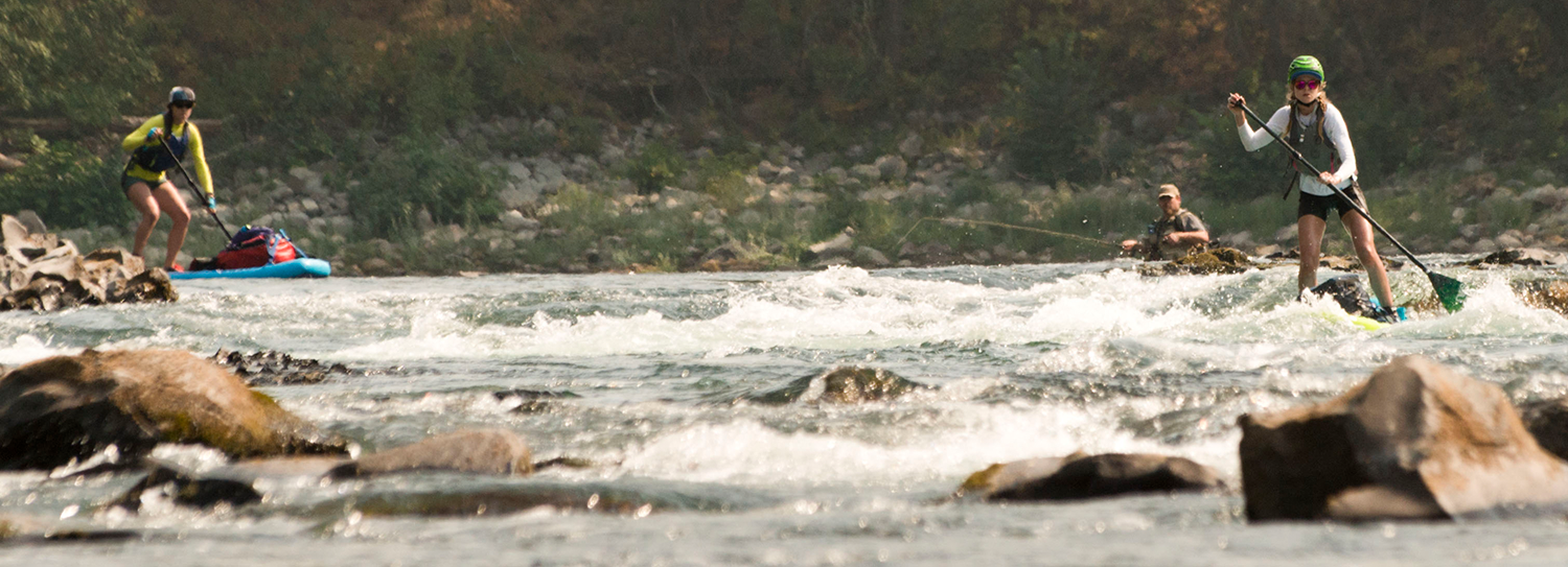 Photo of paddleboarders navigating rapids on the Spokane River.