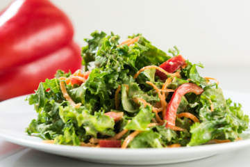 Photo of nutty kale slaw arranged with carrots and bell peppers.