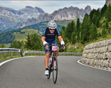 Photo of Russ Lee cycling on a road in Italy.