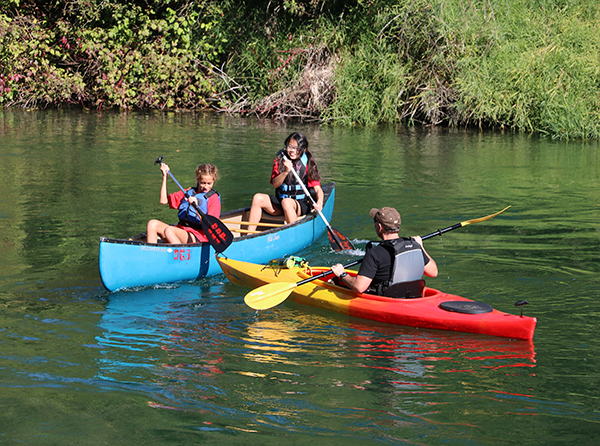 Photo of kids kayaking on a sunny day.