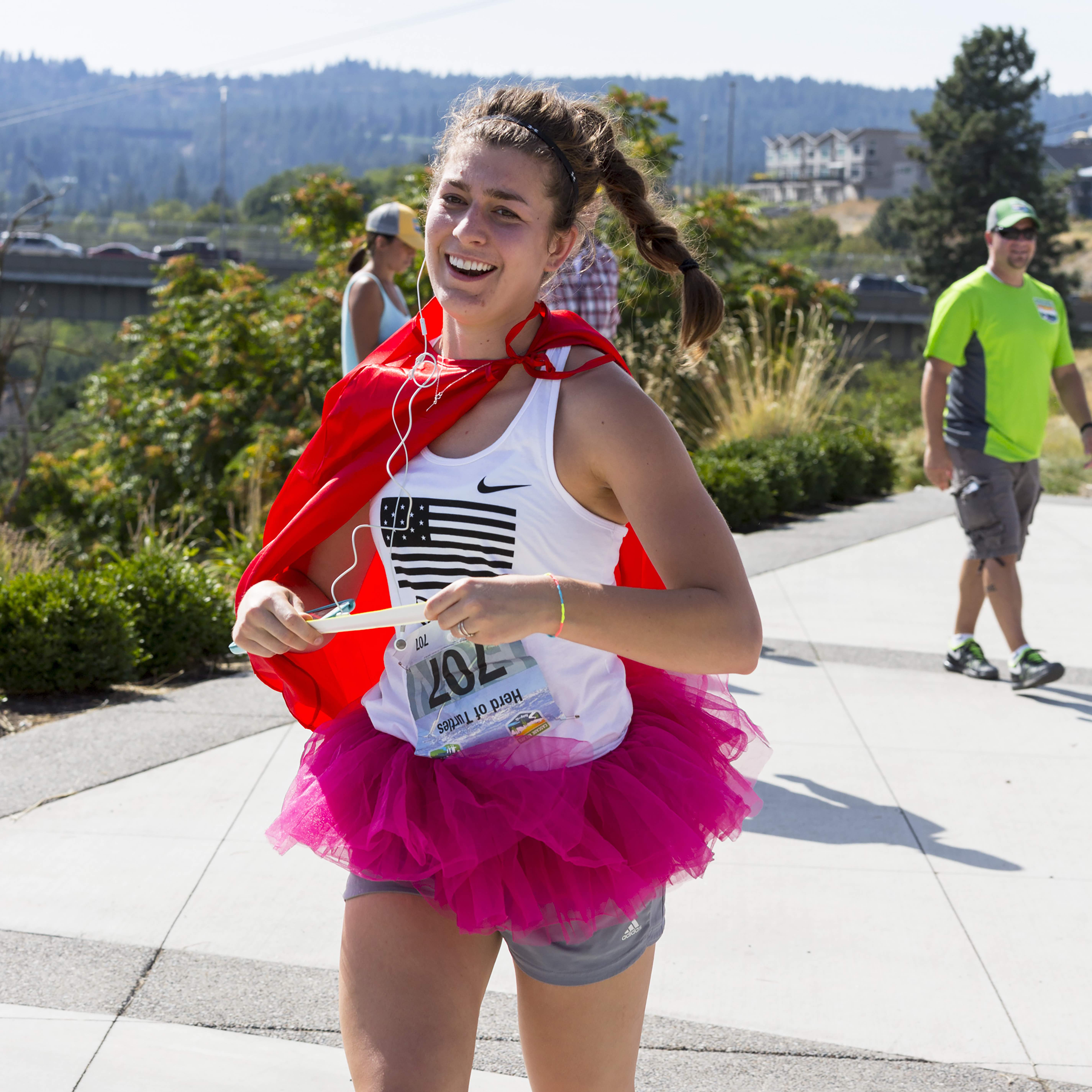 A spirited runner with tutu and cape holds the exchange bracelet for her team.