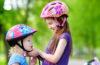 Photo of older kid buckling younger kid's helmet.